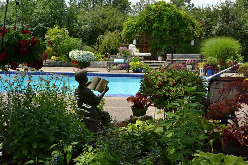 gardens around pool with statue of boy reading in Amherst NY