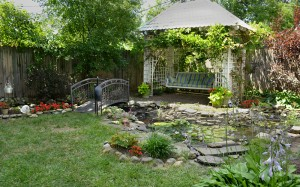 overall view of stream and swing in pergola in Snyder NY backyard