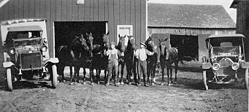 The grandfather and uncle of the current owner, Dr. Frank Meyer, hold the reins of seven horses in this undated photo. They are flanked by two early machines that eventually replaced the horses. The barns burned in the early 1950s and were replaced by the cement block barn that is currently in use on the farm. Photo courtesy Dr. Frank and Linda Meyer