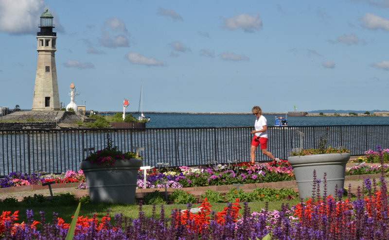 woman walking by test gardens at Erie Basin Marina