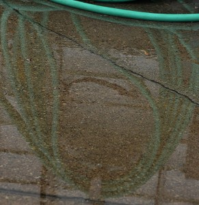 hose reflected in puddle by Stofko
