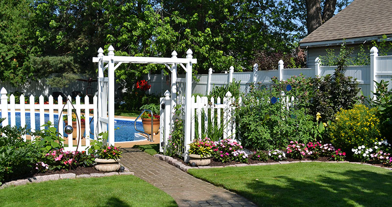 garden beds by fence and pool in Snyder NY